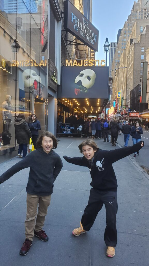 Two boys posing dramatically in front of the Majestic Theater marquee showing the Phantom of the Opera.