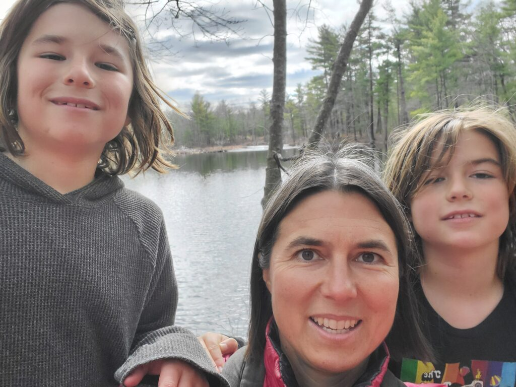 Selfie of mom with twins with messy hair posing in front of a pond at Harold Parker State Forest.
